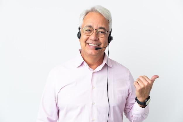 Telemarketer mann mittleren alters, der mit einem headset arbeitet, das auf weißem hintergrund isoliert ist und auf die seite zeigt, um ein produkt zu präsentieren?
