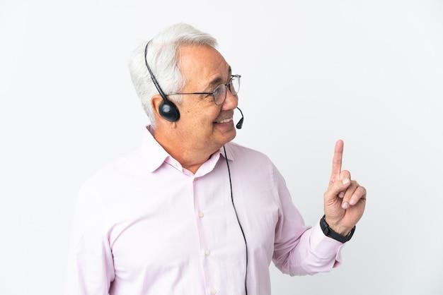 Telemarketer mann mittleren alters, der mit einem headset arbeitet, das auf weißem hintergrund isoliert ist und auf eine großartige idee hinweist