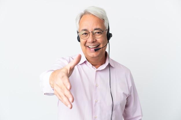Telemarketer mann mittleren alters, der mit einem headset arbeitet, das auf weißem hintergrund isoliert ist und die hände schüttelt, um ein gutes geschäft abzuschließen