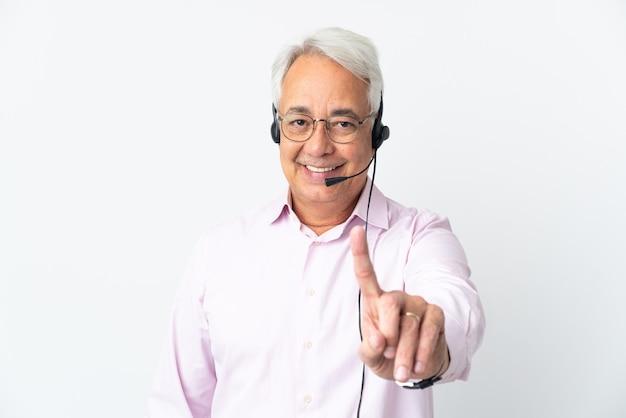 Telemarketer mann mittleren alters, der mit einem headset arbeitet, das auf weißem hintergrund isoliert ist und einen finger zeigt und hebt