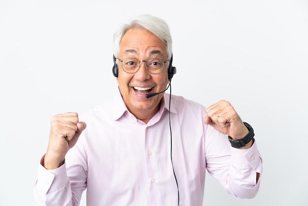 Telemarketer mann mittleren alters, der mit einem headset arbeitet, das auf weißem hintergrund isoliert ist und einen sieg in der siegerposition feiert