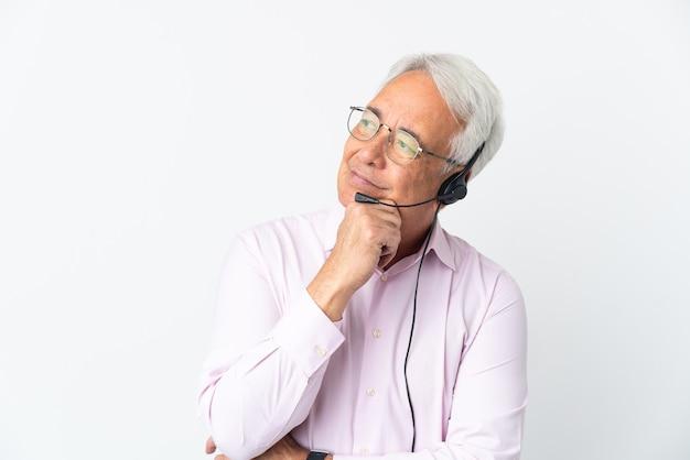 Telemarketer mann mittleren alters, der mit einem headset arbeitet, das auf weißem hintergrund isoliert ist und zweifel hat