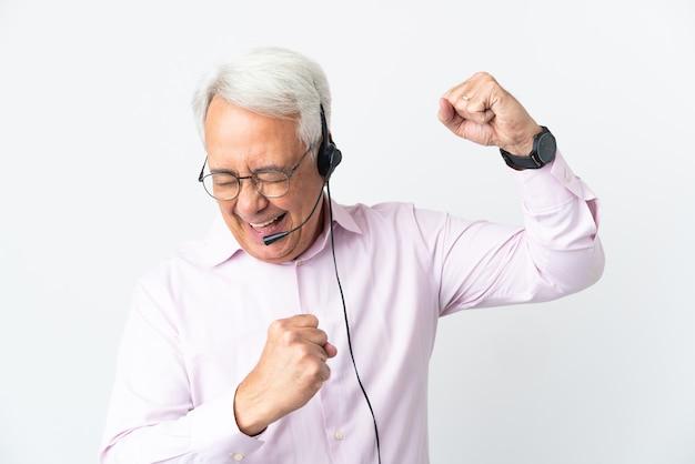 Telemarketer mann mittleren alters, der mit einem headset arbeitet, das auf weißem hintergrund lokalisiert wird und einen sieg feiert