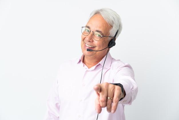 Telemarketer mann mittleren alters, der mit einem headset arbeitet, das auf weißem hintergrund lokalisiert zeigt, zeigt front mit glücklichem ausdruck