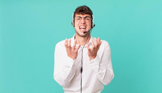 Telemarketer sieht verzweifelt und frustriert, gestresst, unglücklich und verärgert aus, schreit und schreit