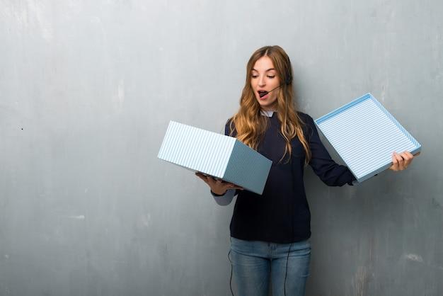 Telemarketerfrau, die geschenkbox in den händen hält