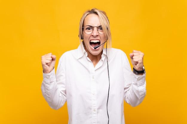 Telemarketerin der jungen frau, die aggressiv mit einem wütenden ausdruck oder mit geballten fäusten schreit, um erfolg zu feiern