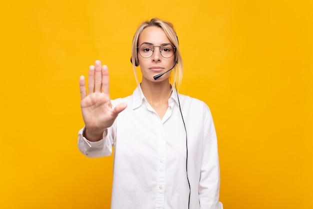 Telemarketerin der jungen frau, die ernst, streng, unzufrieden und wütend aussieht und offene handfläche zeigt, die stoppgeste macht