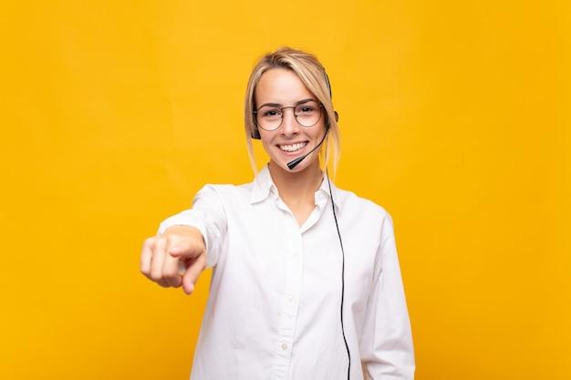 Telemarketerin der jungen frau, die mit einem zufriedenen, selbstbewussten, freundlichen lächeln auf kamera zeigt und sie wählt