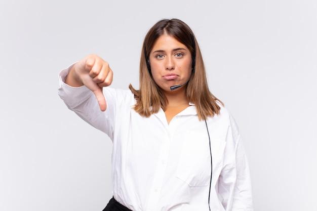 Telemarketerin der jungen frau, die sich böse, wütend, verärgert, enttäuscht oder unzufrieden fühlt und mit einem ernsten blick die daumen nach unten zeigt