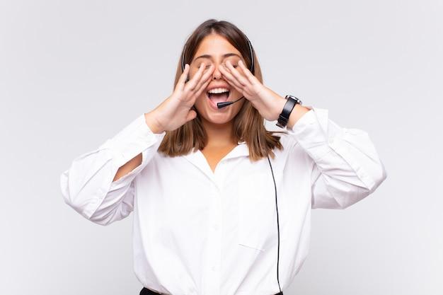 Telemarketerin der jungen frau, die sich glücklich, aufgeregt und positiv fühlt, einen großen schrei mit den händen neben dem mund gibt und ruft