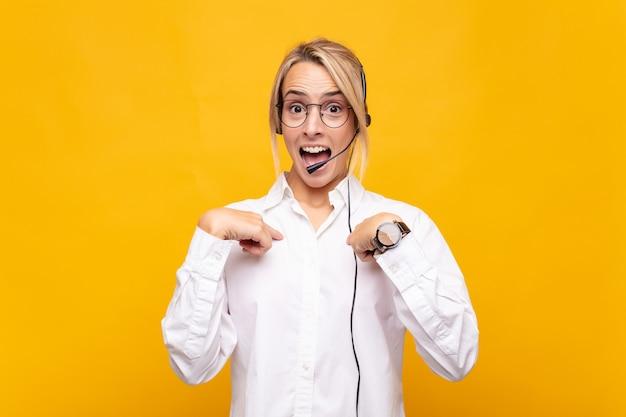 Telemarketerin der jungen frau, die sich glücklich, überrascht und stolz fühlt und mit einem aufgeregten, erstaunten blick auf sich selbst zeigt