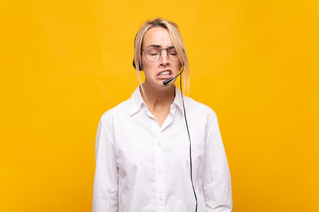 Telemarketerin der jungen frau, die traurig und weinerlich mit einem unglücklichen blick fühlt und mit einer negativen und frustrierten haltung weint