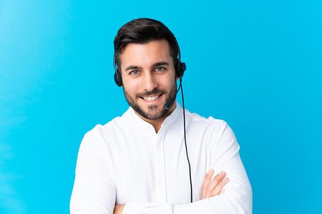 Telemarketermann, der mit einem kopfhörer über dem blauen lachen arbeitet