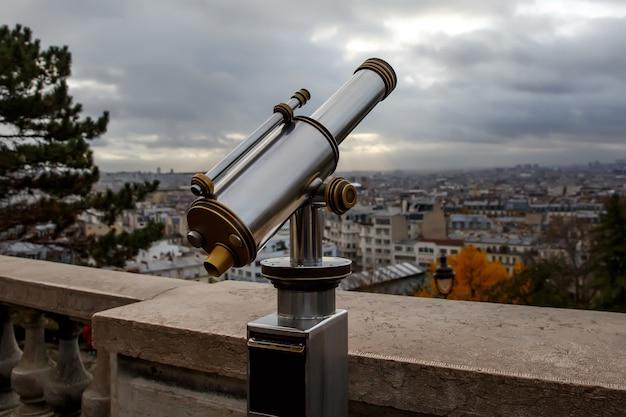 Teleskop mit blick auf paris. bewölkter himmel.