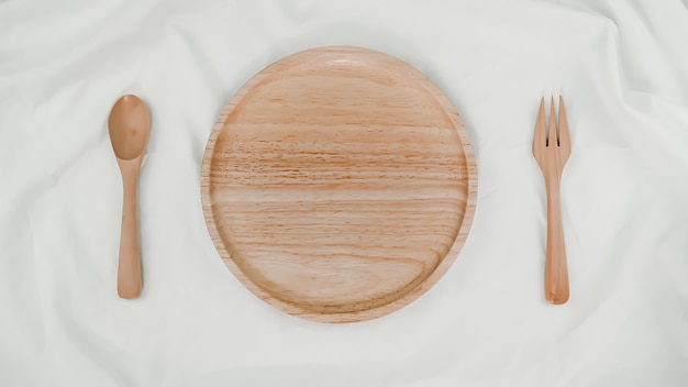 Teller aus holz, löffel aus holz und gabel aus holz auf weißem stoff. draufsicht der tabelleneinstellung auf weißem hintergrund