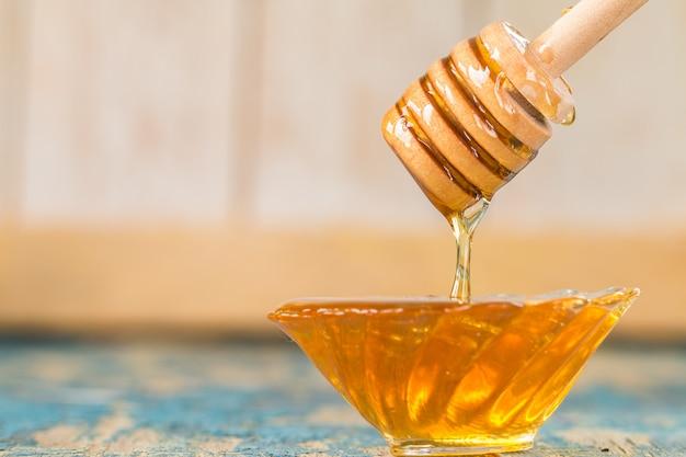 Teller des honigs mit hölzernem löffel