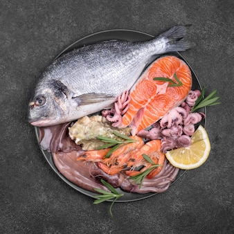 Teller gefüllt mit frischem ungekochtem fisch mit meeresfrüchten