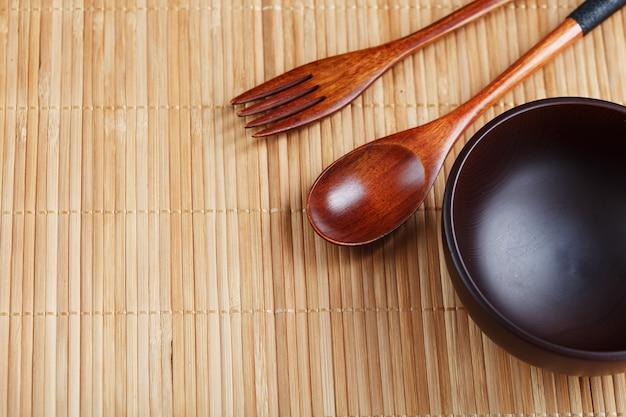 Teller, löffel und gabel aus naturholz auf bambusunterlage. asiatisches lebensmittelhandwerkskonzept. von oben betrachten