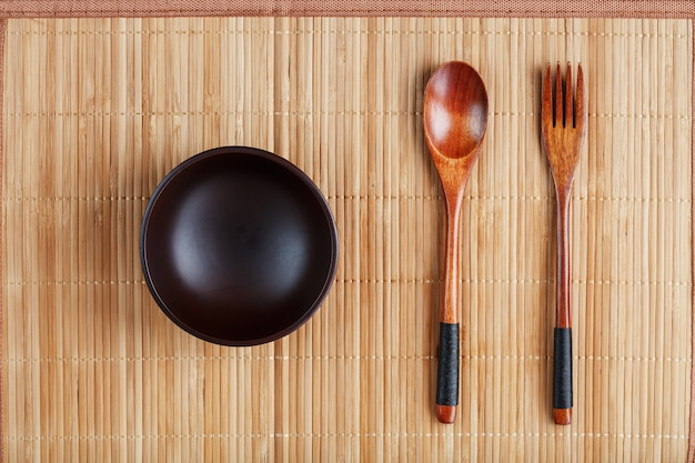 Teller, löffel und gabel aus naturholz auf bambusunterlage.