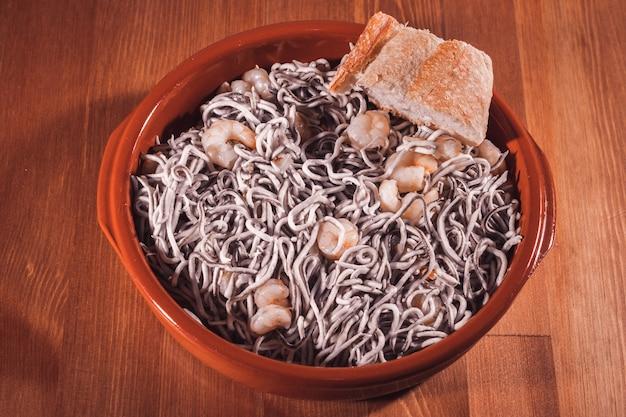 Teller mit aalen mit garnelen in einer traditionellen tonplatte auf einem holztisch