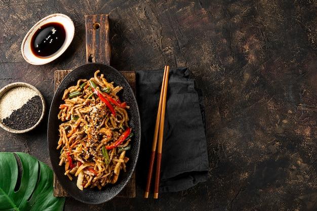 Teller mit asiatischen buchweizen-soba-nudeln mit gemüse, pilzen und hühnchen auf dunklem hintergrund