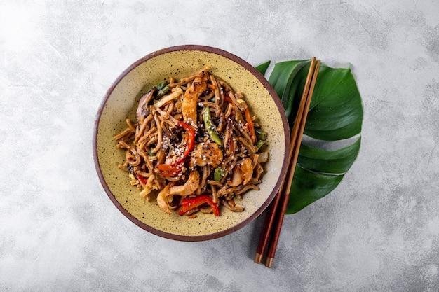Teller mit asiatischen buchweizen-soba-nudeln mit gemüse, pilzen und hühnchen auf hellgrauem hintergrund
