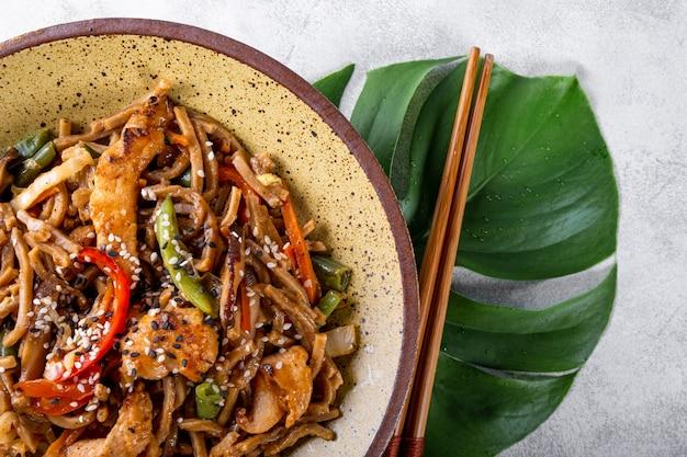 Teller mit asiatischen buchweizen-soba-nudeln mit gemüse, pilzen und hühnchen