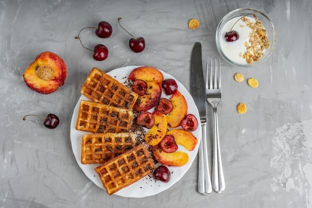 Teller mit belgischen waffeln und kirschen- und pfirsichscheiben zusammen mit joghurt und besteck. draufsicht
