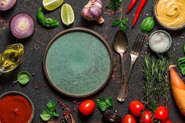 Teller mit besteck im rahmen aus frischem gemüse, gewürzen, kräutern und saucen auf schwarzem steintisch