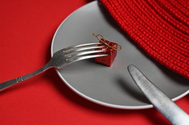 Teller mit besteck und geschenk auf rotem grund. foto in hoher qualität