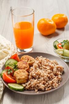 Teller mit buchweizen, gebratenen fleischkoteletts, frischen gurkenstücken, tomaten und frischer petersilie, gabel, salat aus frischen gurken und tomaten in glasschüssel, glas orangensaft und orangen.