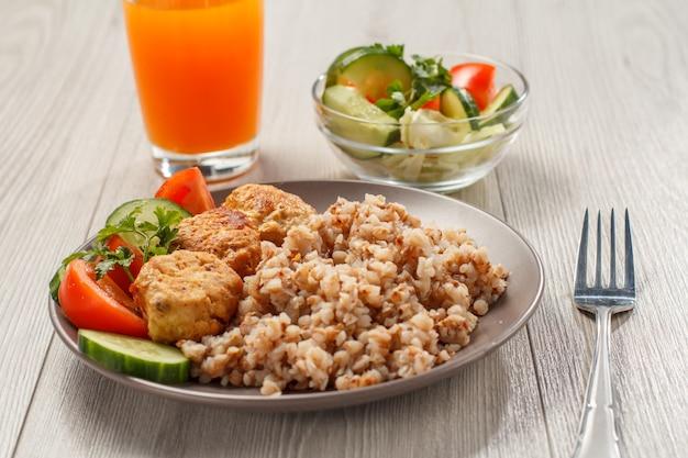 Teller mit buchweizen, gebratenen fleischkoteletts, frischen gurkenstücken, tomaten und frischer petersilie, gabel, salat aus frischen gurken und tomaten in glasschüssel und glas orange.