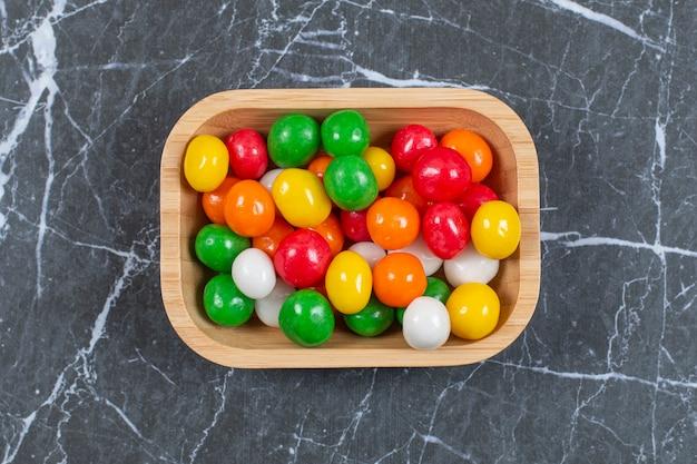 Teller mit bunten bonbons auf marmor.