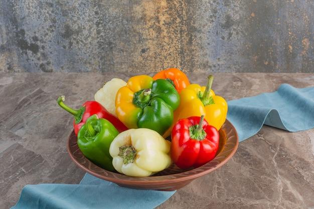 Teller mit bunten frischen paprika auf marmoroberfläche