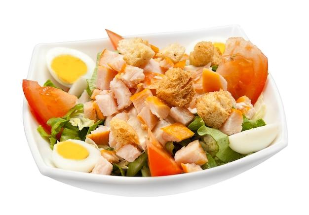 Teller mit caesar-salat mit hähnchenfilet und parmesan-käse auf einem weißen teller. isoliertes objekt