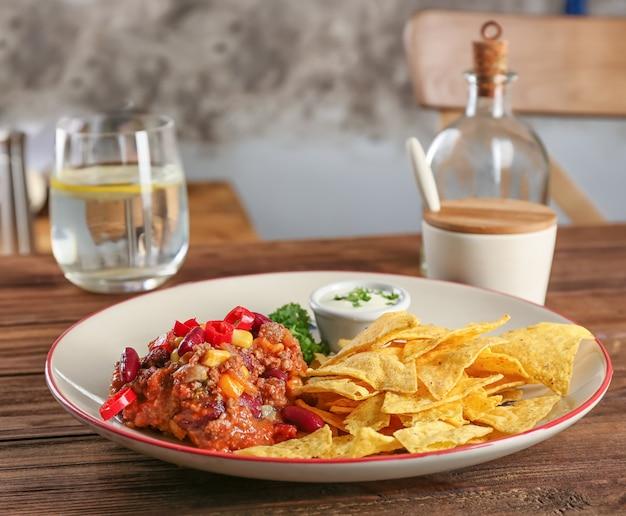 Teller mit chili con carne und nacho-chips auf dem tisch