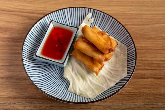 Teller mit chinesischen mini-frühlingsrollen mit süß-sauer-sauce