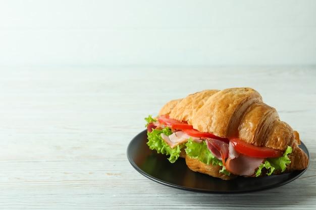 Teller mit croissant-sandwich auf weißem holztisch