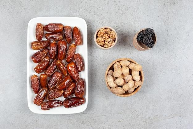 Teller mit datteln neben schalen mit erdnüssen und maulbeeren auf marmoroberfläche. hochwertige illustration