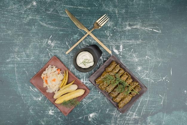 Teller mit dolma und sauerrahm mit salzgurke und kohl auf marmoroberfläche