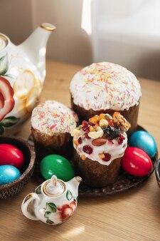 Teller mit drei traditionellen orthodoxen osterkuchen und bemalten roten, grünen und blauen eiern sowie vintage-blumenteekannen