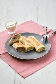 Teller mit dünnen pfannkuchen gefüllt mit hasenhackfleisch