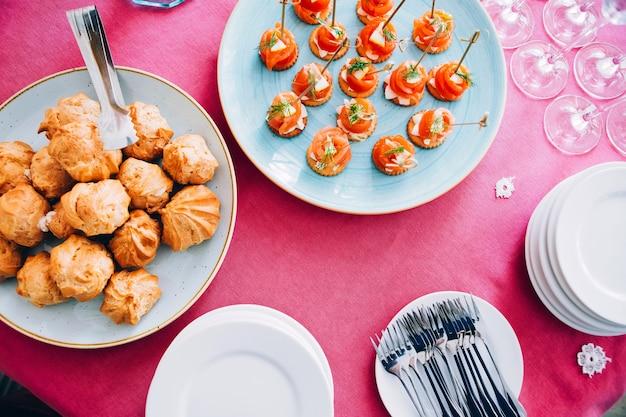 Teller mit eclairs auf dem tisch. teller auf einer rosa tischdecke. canape mit rotem fisch. weißes geschirr, gabeln, weingläser. von oben betrachten