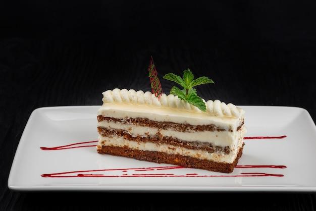 Teller mit einem stück köstlicher karamell-sahne-torte, dekoriert mit minzblättern auf schwarzem holzhintergrund