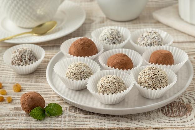 Teller mit energiebissen mit kakaopulver, sesam und kokosflocken auf weißem holztisch