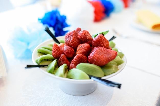 Teller mit erdbeeren und kiwi.