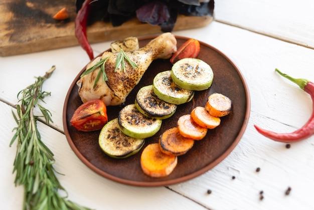 Teller mit essen auf dem tisch, gegrilltem gemüse und hähnchenschenkel