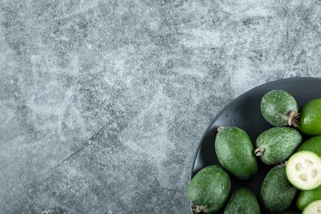 Teller mit feijoa-früchten auf marmor.