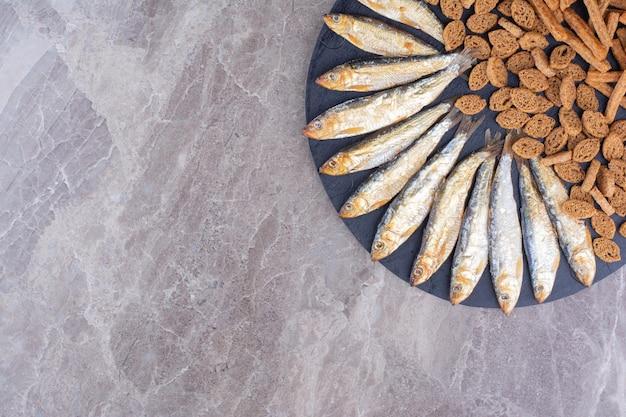 Teller mit fisch- und crackersnacks auf marmoroberfläche. foto in hoher qualität